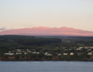 The sun spread a red glow on the Mauna Lea Observatories.